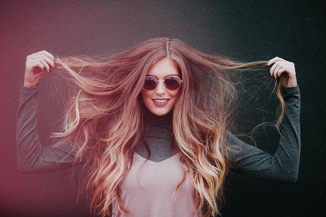 žena si drží dlouhé vlasy